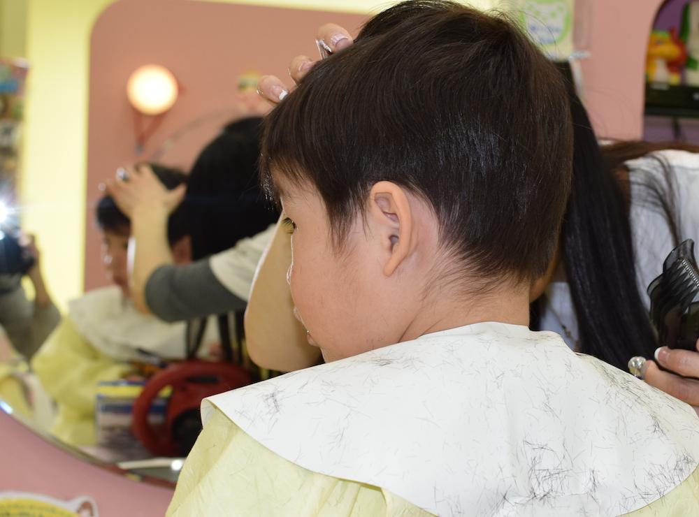 美容師さんに聞くテスコムのバリカンヘアーカッターTC470の使いかた【耳周り】お子さんの耳を押さえながら、耳の形に沿ってカット・カット後うしろからの写真:もみあげの位置にある産毛は自然に残すとよいでしょう。